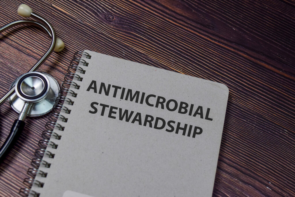 Book about (AMS) Antimicrobial Stewardship isolated on wooden ta